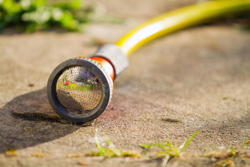 Garden hose on the ground. Yellow garden hose on the ground royalty free stock photos