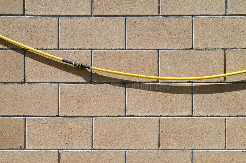 Download The Garden Hose With The Repair Coupling Hangs On A Wall From  Smooth Stone Blocks