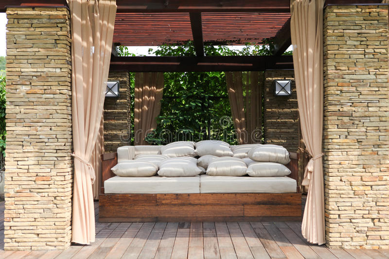 Garden house. Garden brick house with wooden couch and white pillows stock photography