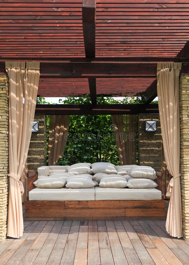 Garden house. Garden brick house with wooden couch and white pillows stock images