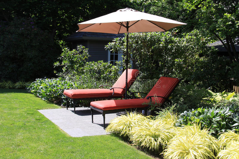 Garden lounge chairs. With umbrella royalty free stock photo
