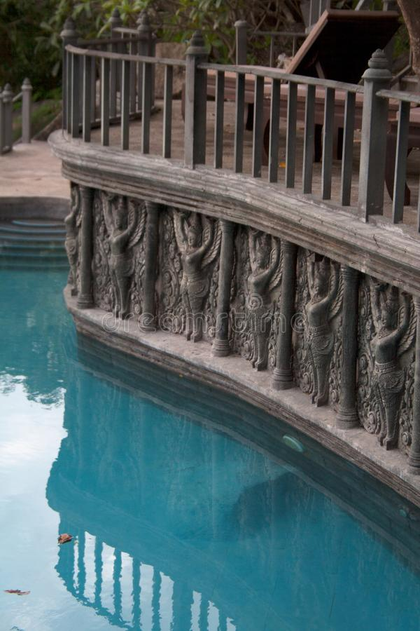 Garden lounge pool with stone sculptures and pilasters. Garden lounge pool surrounded by stone sculptures and pilasters with a terrace balcony above royalty free stock photos