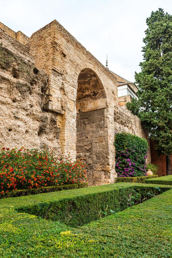 Garden and massive stone wall at Real Alcazar royalty free stock photography