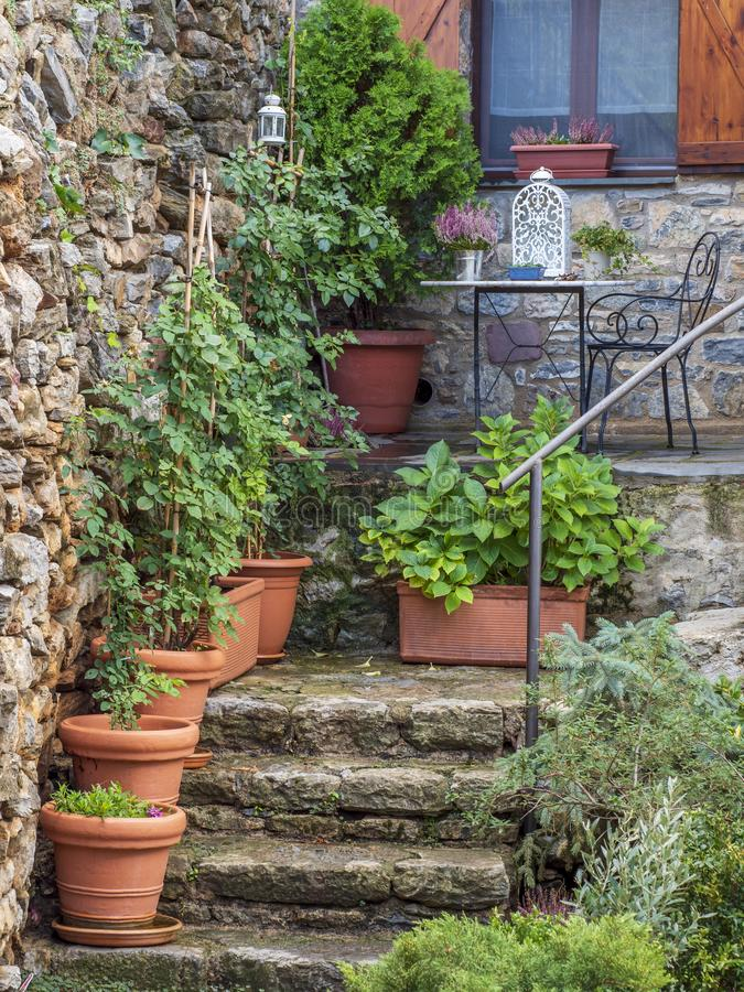 A garden with a natural stone staircase decorated with plant pots, with a small terrace above it royalty free stock photos