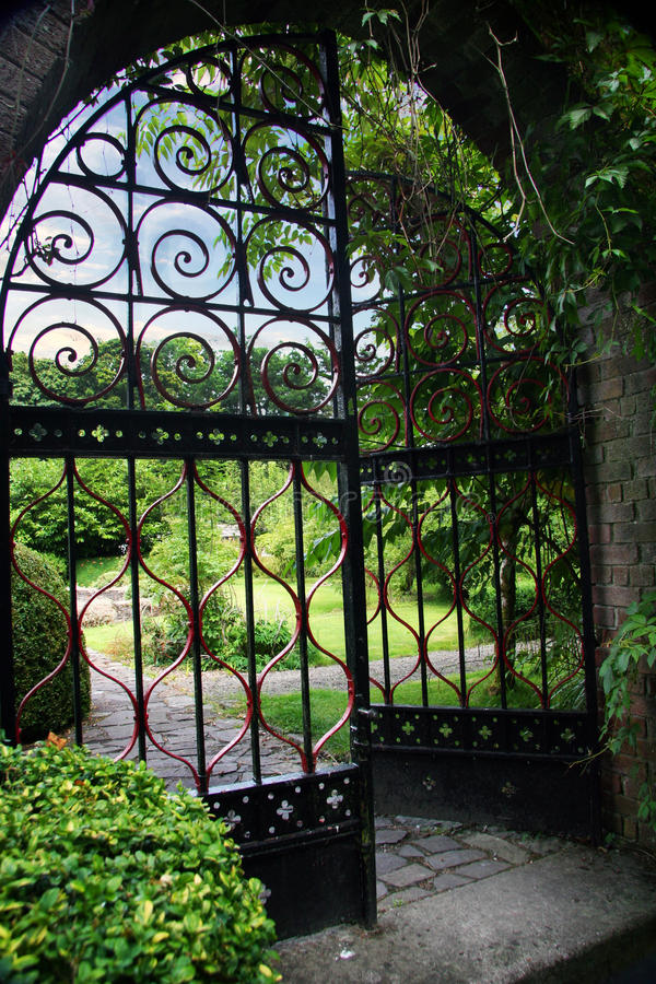 Garden with an Open Gate. Gate to a pretty private garden with bushes and trees