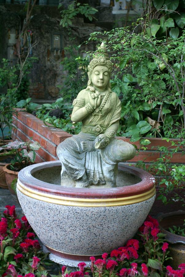 Garden ornament of an Asian statue. A garden ornament decoration of an Asian statue in a pot and Celosia Caracas flowers stock images