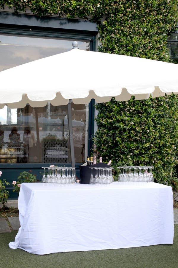 Garden party set: white table  sun umbrella wine bottles  and glasses in an elegant garden ready for the party. Garden party set: white table and sun umbrella stock photos