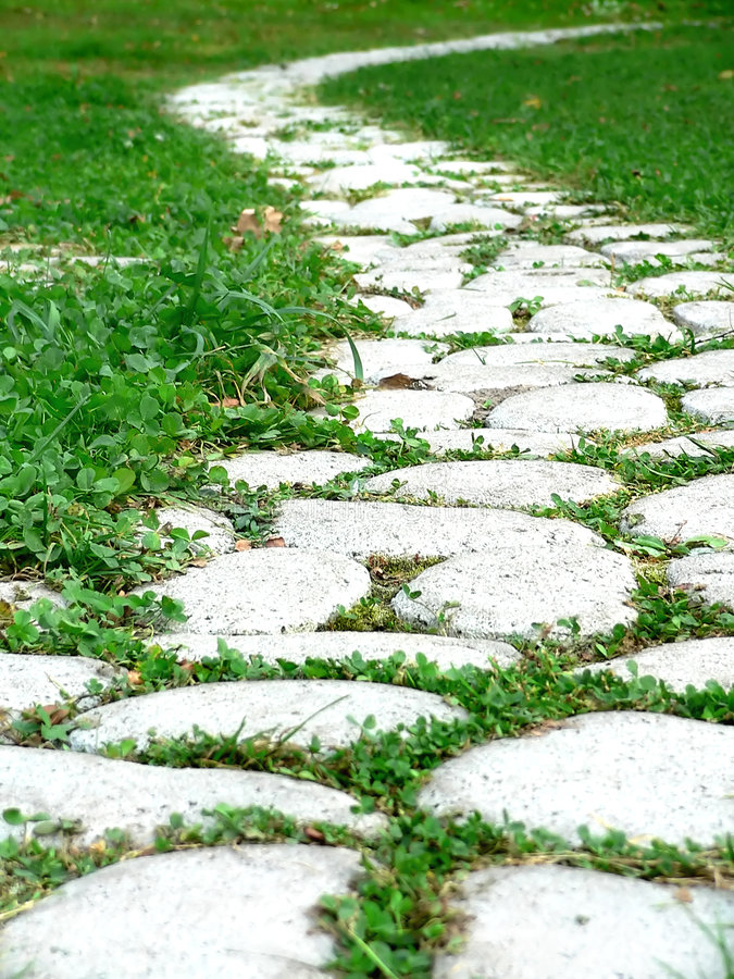 Garden path. Garden stone path with grass growing up between the stones