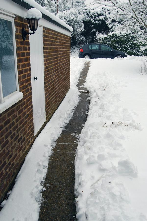 Garden path cleared through snow from house to car. Domestic winter scene of garden path cleared through snow from house to car stock image