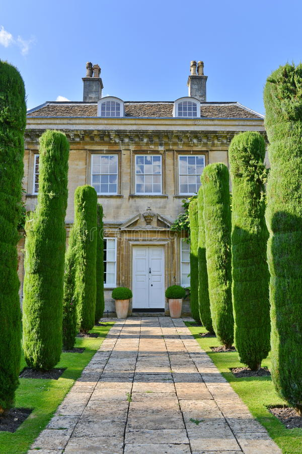 Garden Path of a Country House. View of a Tree Lined Garden Path Leading to a Beautiful Old English Country Mansion House royalty free stock photography