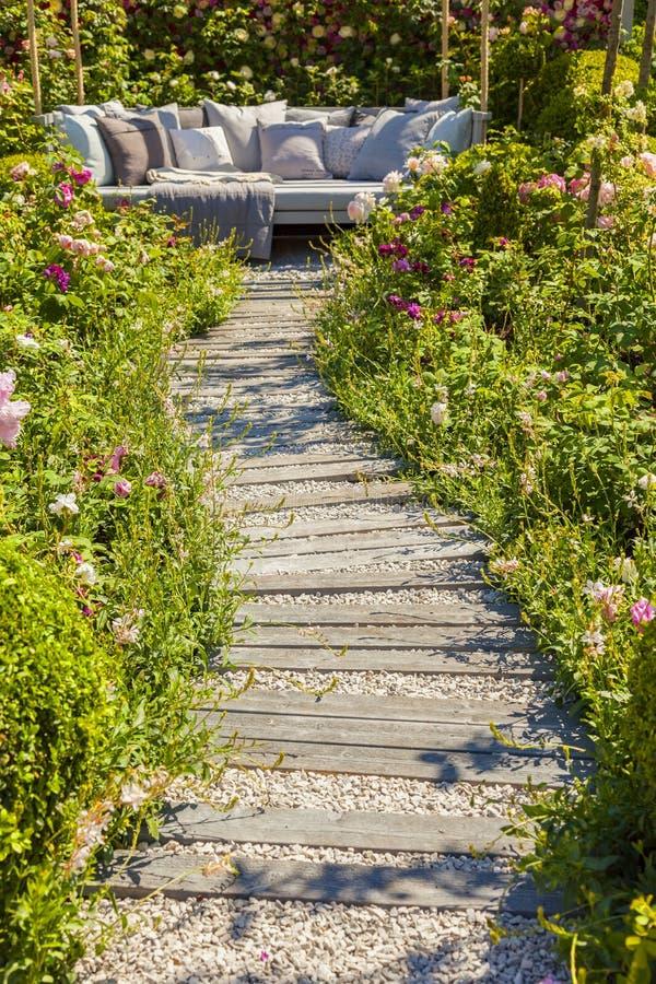 Garden path leading to seating area. Garden path leading to comfy seating area royalty free stock photos