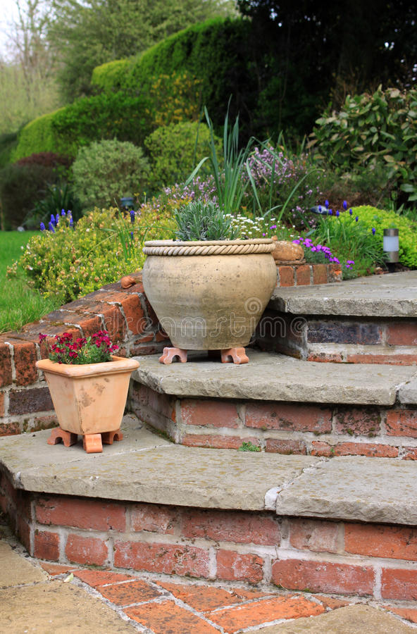 Garden Patio. The corner of a set of stone and brick constructed steps leading to and from a garden patio area with two terracotta pots on the steps. Various stock image