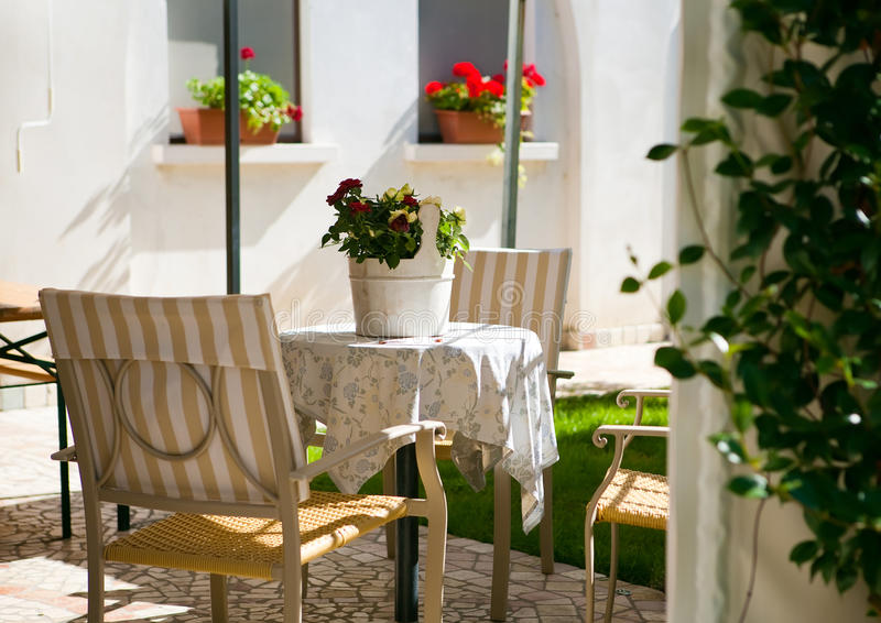Garden patio. With casual chairs & small round table, decorated with roses' pot, a lovely place to relax stock photography