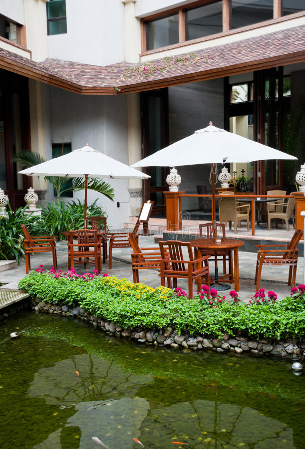 Garden patio. With armchairs and umbrellas by the waterside royalty free stock photography