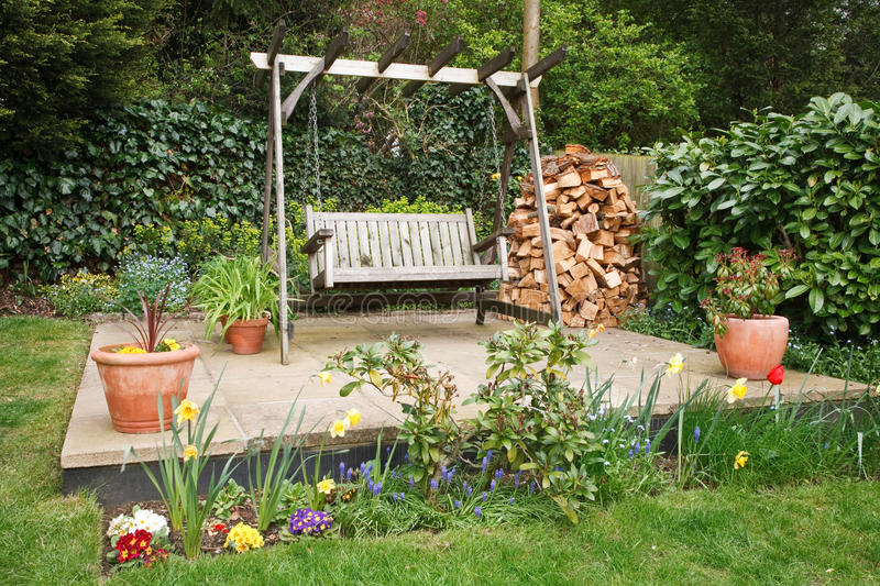 Garden patio. Relaxing garden patio with swing bench, potted plants and a wood pile stock image