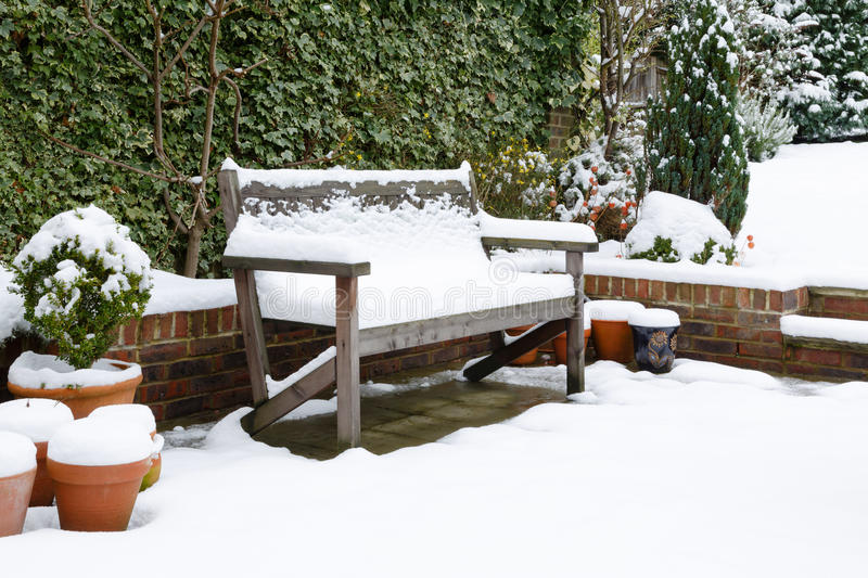 Garden patio bench with snow. Snow covered garden bench on a patio in winter stock image