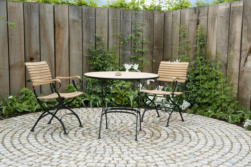 Garden patio with round table and two chairs. Hidden garden patio with table and chairs in front of wooden planks with creeing plants royalty free stock photography