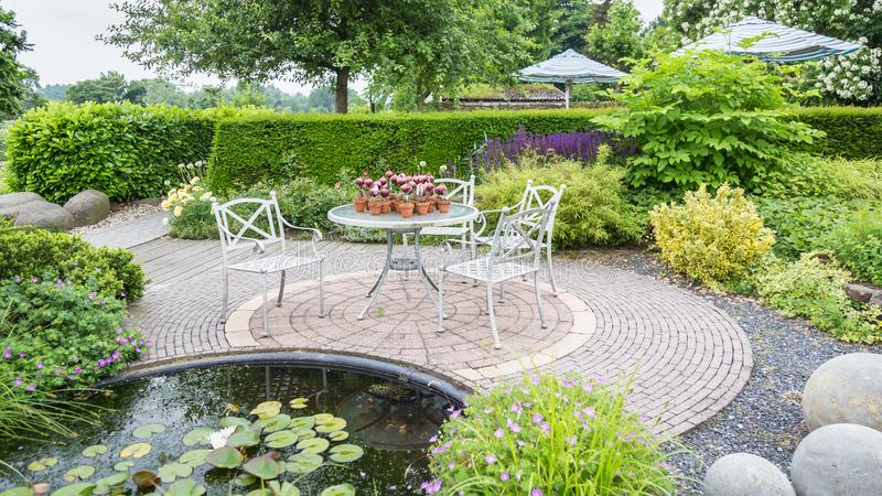 Garden design with pond and patio. Garden with pond and classic white chairs and table on a patio royalty free stock images