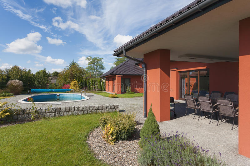 Garden pool and house. A garden of a rich house with a swimming pool stock images