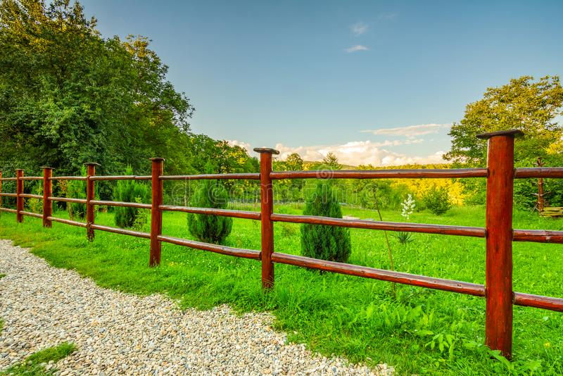 Garden red wooden fence and green grass. And trees with clear sky royalty free stock photos
