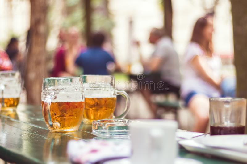 Garden restaurant, glass of beer on table royalty free stock image