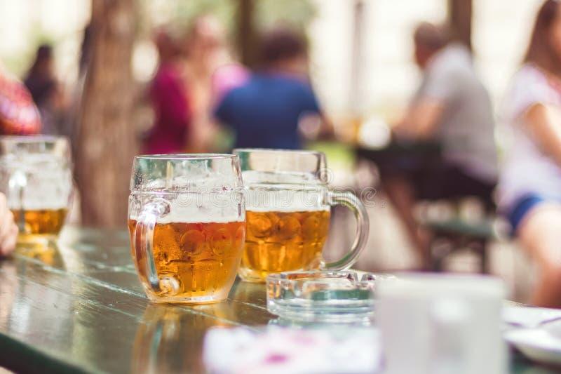Garden restaurant, glass of beer on table stock image