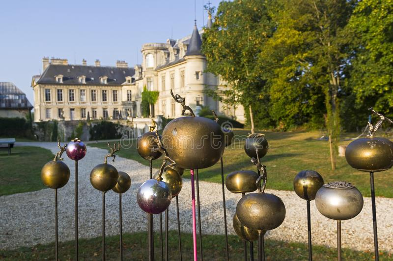 Garden sculpture in French Castle. Garden sculpture - dancing figures on the balls. Bronze. Castle Grand Mello. France. Sunny day in August royalty free stock image