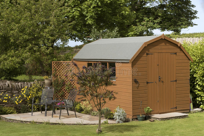 Garden shed and patio with seating. A Dutch barn style garden shed with a patio in a English country garden stock images