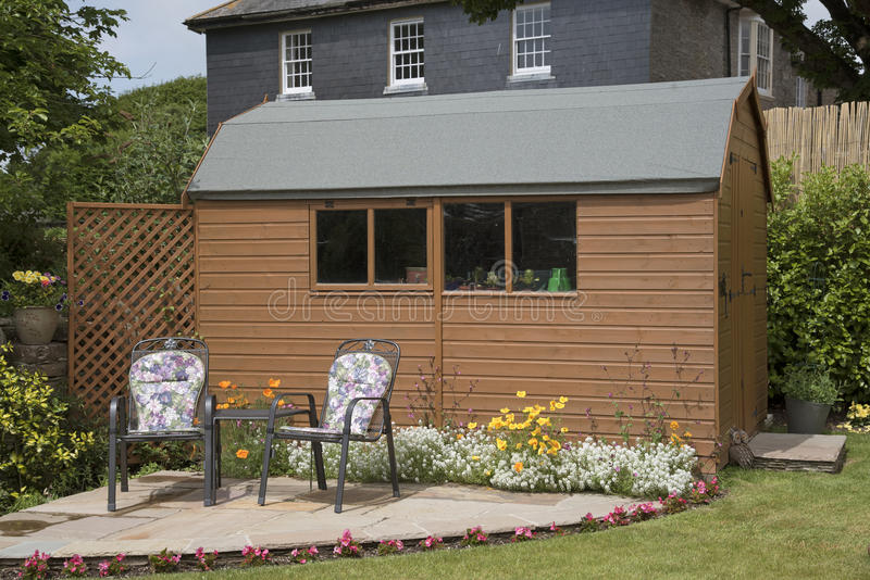 Garden shed and a small patio. DEVON ENGLAND UK - JUNE 2016 - A barn style garden shed with a small patio and chairs royalty free stock photos