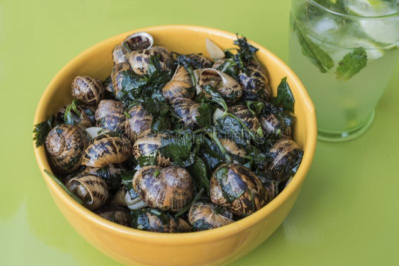 Garden snails cooked French style in butter with parsley and garlic, in a yellow ceramic bowl with a glass of Mojito on a green ta. Ble royalty free stock images