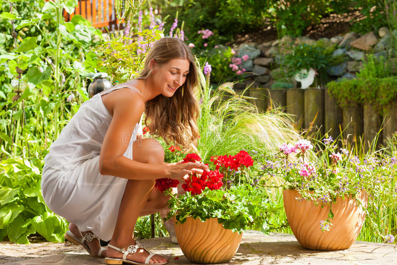 Garden in summer – happy woman with flowers. Gardening in summer - happy woman with flowers and hat in her garden royalty free stock photography