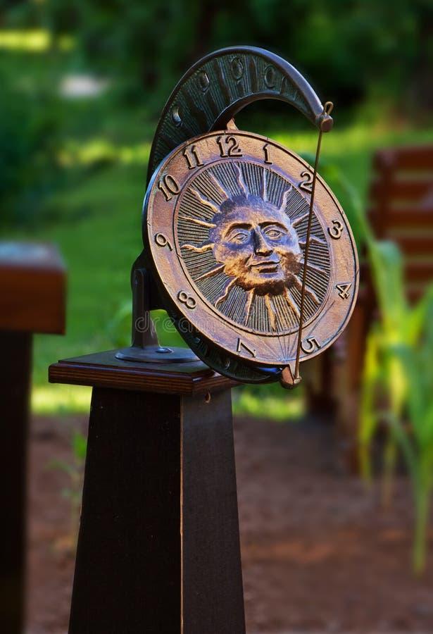 Garden sundial clock. Details of circular garden sundial clock with face of sun royalty free stock images