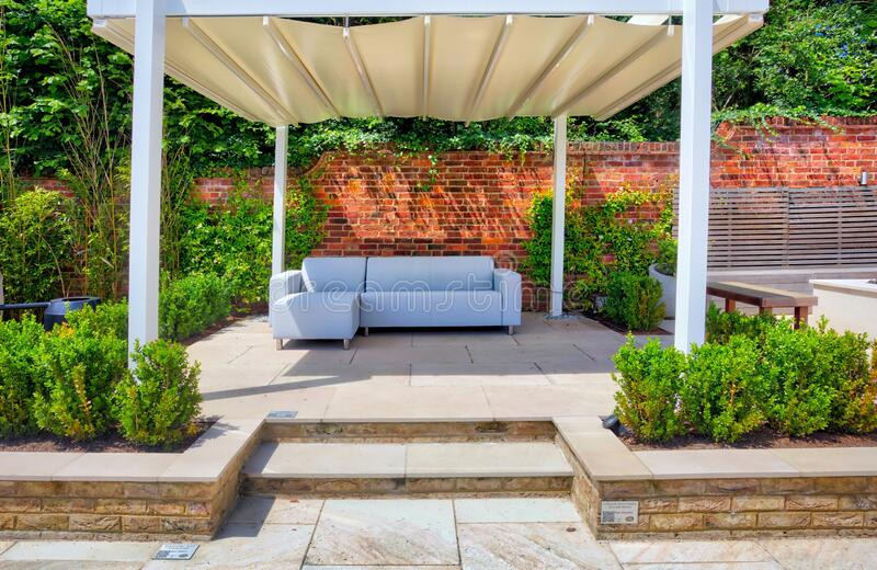 Garden with sunshade area. Peaceful paved garden with large sun shaded seating area and brick wall royalty free stock photography