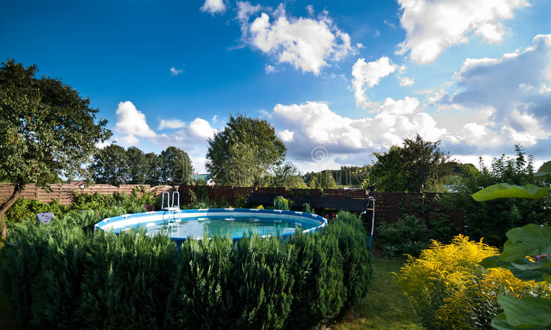Garden and swimming pool. Walled garden with flowering plants and small trees surrounding a circular swimming pool royalty free stock photos