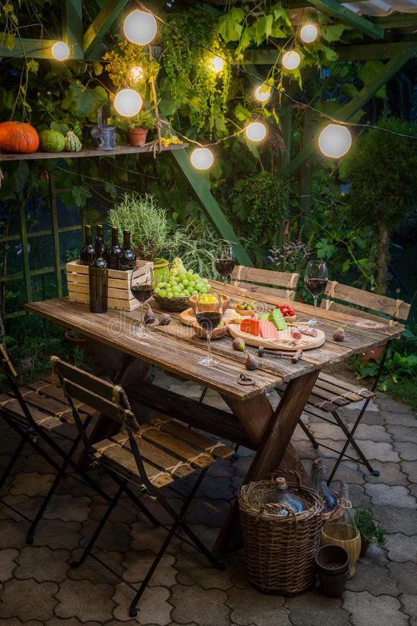 Garden table with appetizers and wine in the evening. Session in outside royalty free stock photography