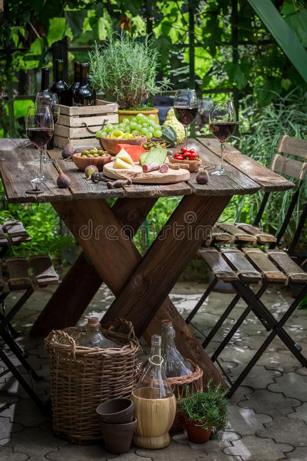 Garden table with snacks and wine in the evening. Session in outside royalty free stock image