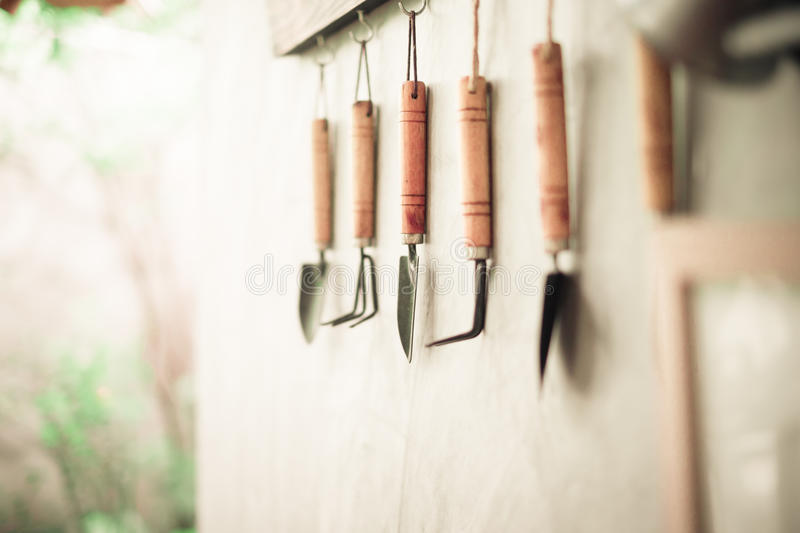 Garden tool hanging on concrete wall with wooden label stock photo