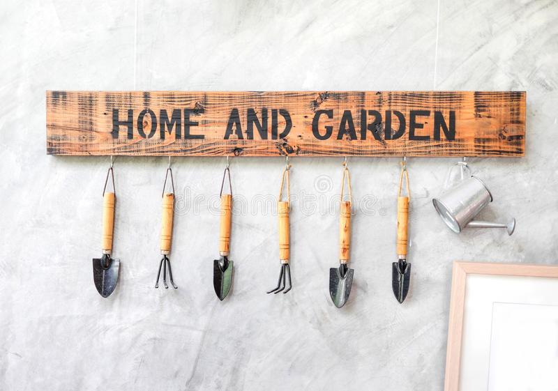 Garden tool hanging on concrete wall with wooden label royalty free stock photo