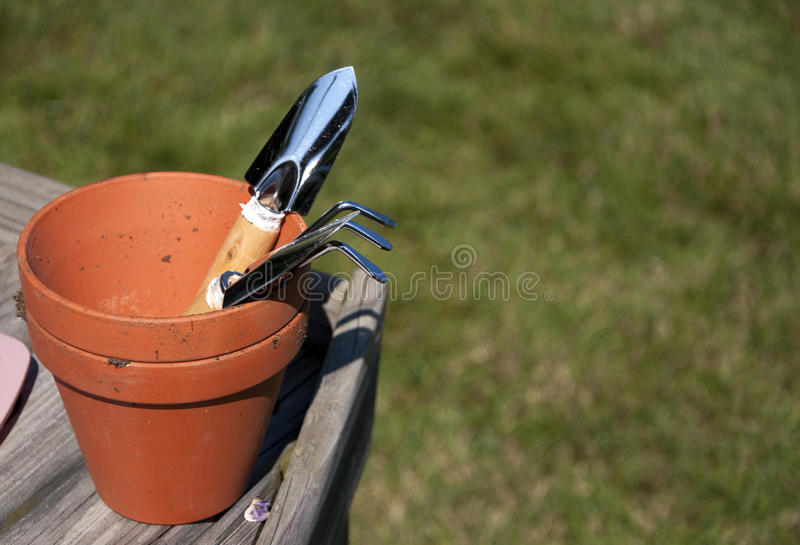 Garden tools. In a clay pot royalty free stock image