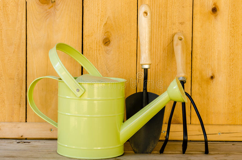 Garden Tools. With watering can, trowel, and hand cultivator on wood background royalty free stock photography