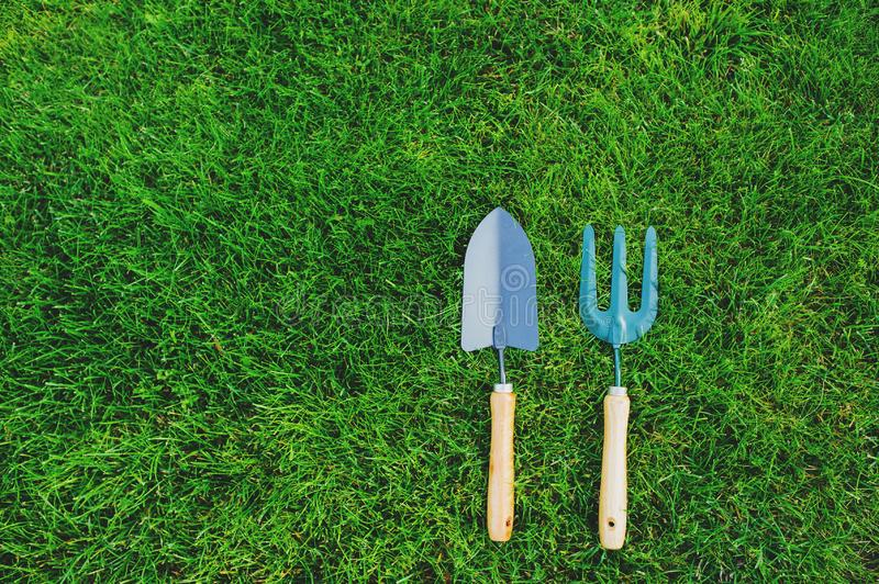 Garden tools on green lawn background. Seasonal spring or summer yard work concept. Growing and seeding royalty free stock photo