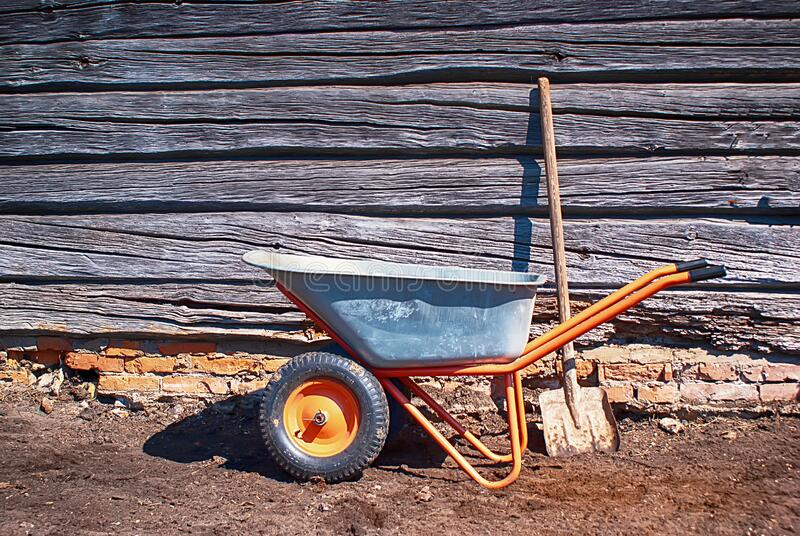 Garden tools stand on the ground next to an old wooden shed on a Sunny day. metal garden wheelbarrow with a shovel, selective focu stock image