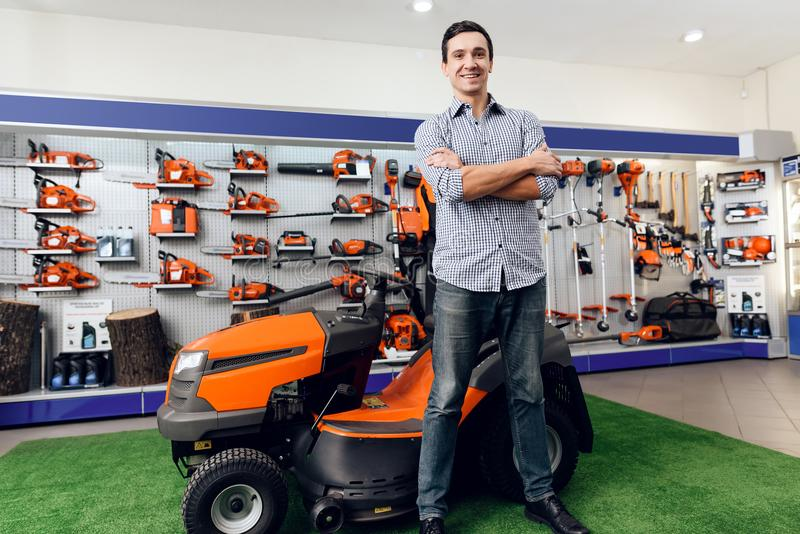 A man is standing near a lawn mower. He is in the garden tools store. There are many tools for gardening here. The guy is smiling stock photography