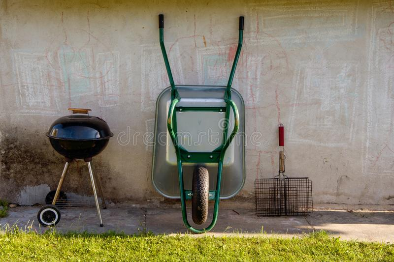 Garden tools, trolley, grill and barbecue stand against the wall royalty free stock images