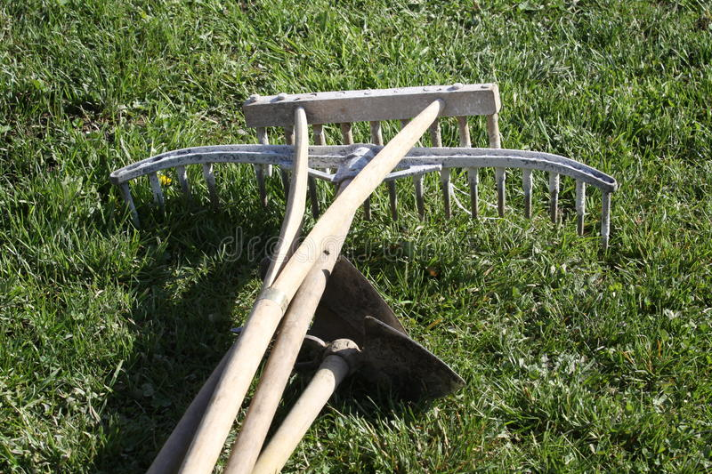 Garden tools in wood. Simple wooden garden tools for the preparation of the spring flowerbeds and reconstruction of turfgrass stock photos