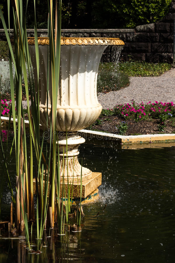 Garden water fountain in pond with reeds stock image