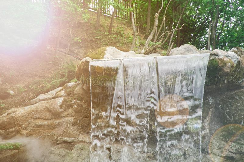 Garden waterfall of stones. Water flows through the stone. The morning sun shines on the waterfall. stock photo