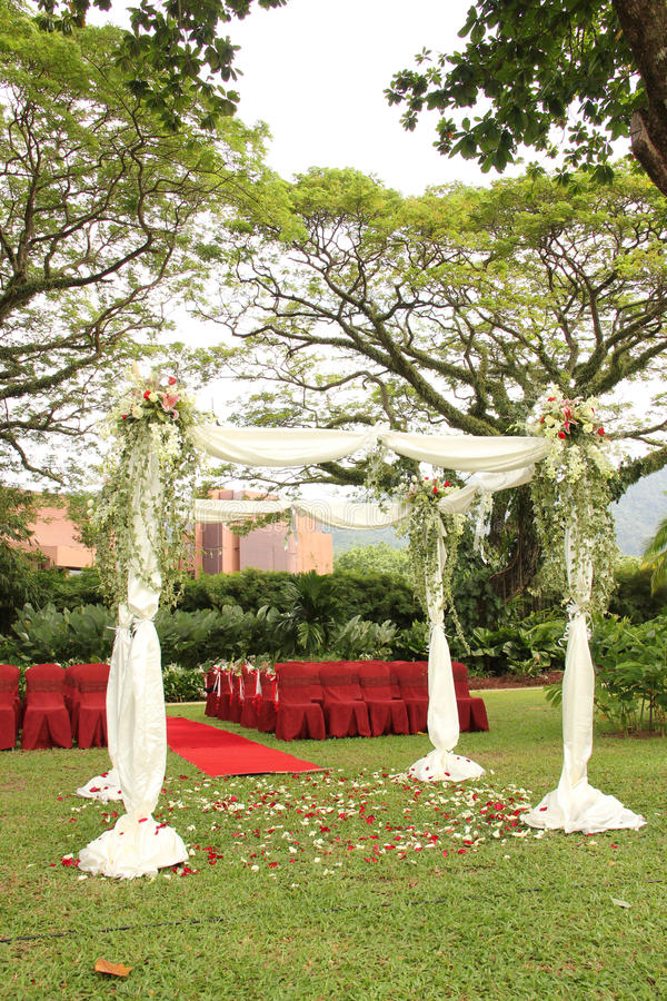 Garden wedding arch decoration. Red with flowers royalty free stock images