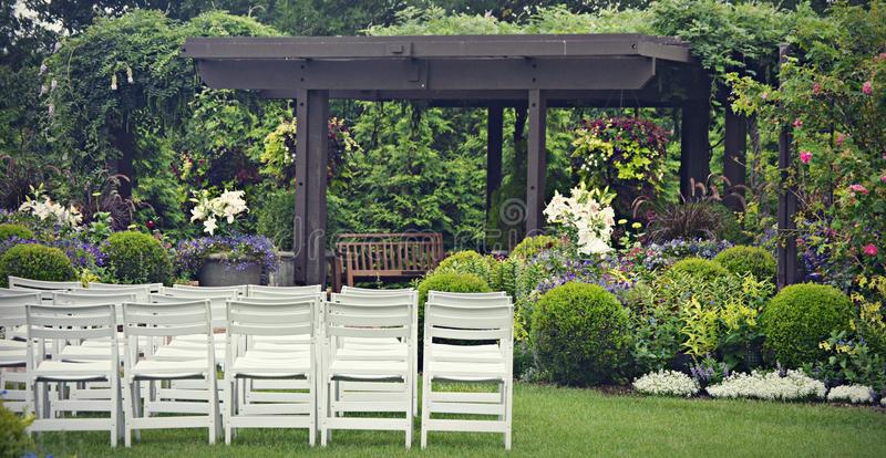 Garden Wedding. A garden wedding set up with white chairs on the lawn surrounded by a black wooden arbor and gorgeous flowers stock photography