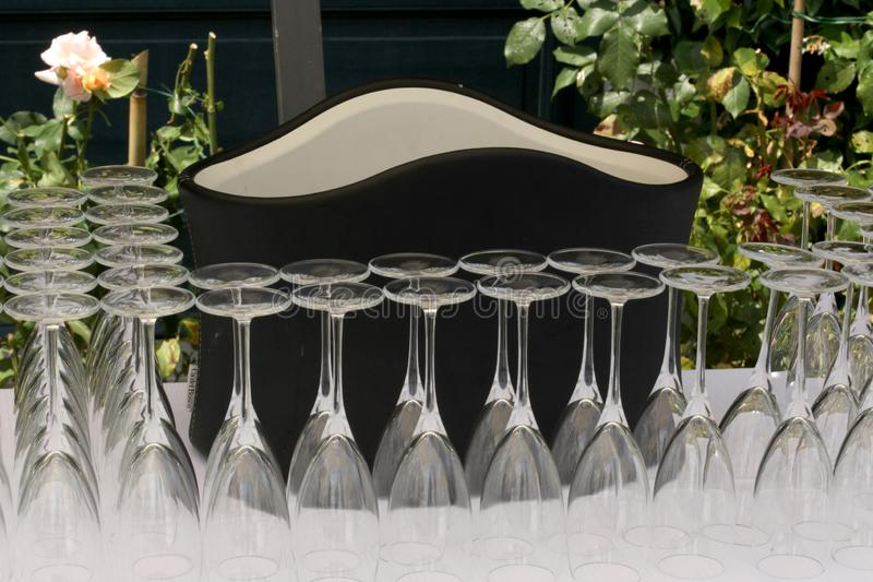 Garden party set: container for cold wine and a line of flute glasses. Garden wine party set: container for cold wine and a line of flute glasses royalty free stock photos